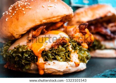 A cheeseburger with bacon and lettuce in a brioche bun #1323101543