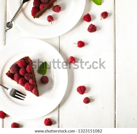 Chocolate cake. Slice of chocolate cake with fresh raspberry served on plate, top view, copy space #1323151082
