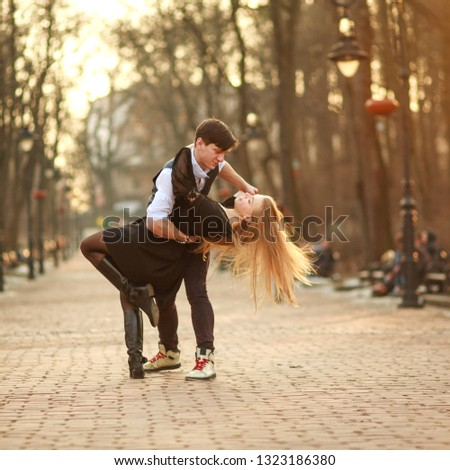 Elegant young couple in love in a classic style passionately dancing in the city park at sunset #1323186380