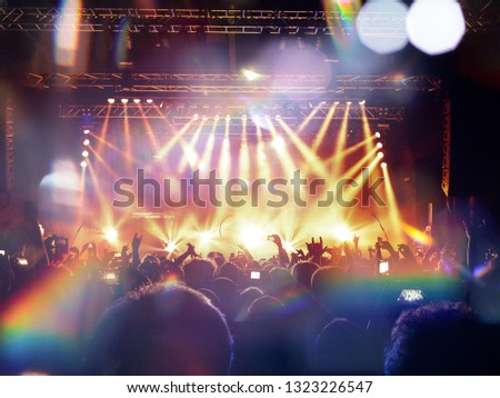 Concert spectators in front of a bright stage with live music #1323226547