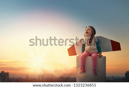 Little child playing pilot. Girl on the background of sunset sky. Kid in an astronaut costume dreaming of becoming a spaceman. #1323236855