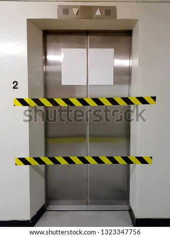 Under maintenance or out of service elevator with No entry barriers tape.