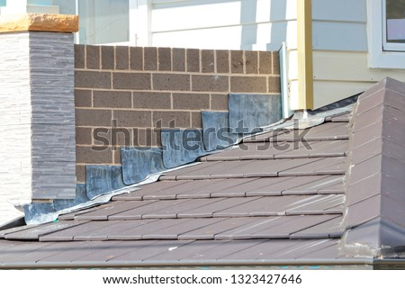 Lead flashing on slate style roof Royalty-Free Stock Photo #1323427646