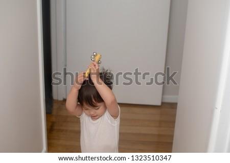 Little boy rises the bells, music instrument over head #1323510347