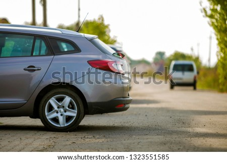 Bukovel, UKRAINE- June 25, 2018: Side view of silver car parked in paved parking lot area on blurred suburb road background on bright sunny day. Transportation and parking concept. #1323551585