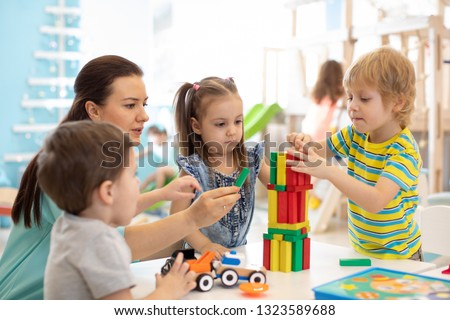 Little kids build wooden toys at home or daycare. Kids playing with color blocks. Educational toys for preschool and kindergarten children. #1323589688