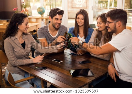 Group of friends hanging out and making a toast with beer  #1323599597