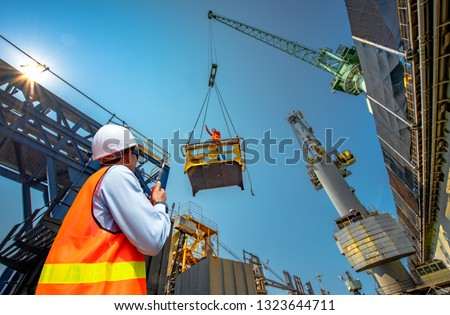 foreman, supervisor, worker, loading master in works at job site, control to the teamwork by walkie talkie radio for job done in the same direction, working at risk and high level of insurance #1323644711