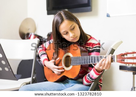 Girl developing skill of playing guitar during extracurricular activity session in school #1323782810