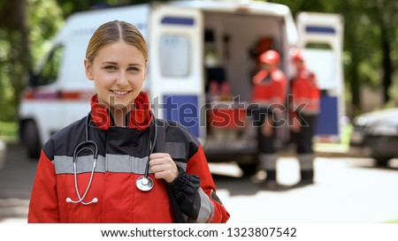 Female paramedic smiling into camera, ambulance crew blurred on background #1323807542