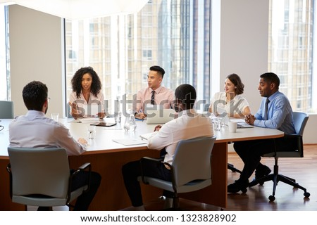 Group Of Business Professionals Meeting Around Table In Modern Office Royalty-Free Stock Photo #1323828902