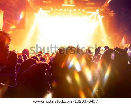 Concert spectators in front of a bright stage with live music #1323878459