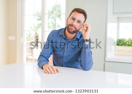Handsome man wearing glasses and smiling relaxed at camera #1323903131