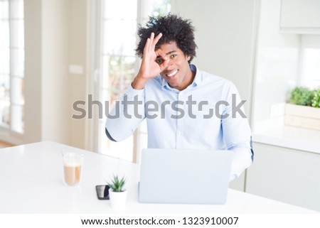 African American business man working using laptop with happy face smiling doing ok sign with hand on eye looking through fingers #1323910007