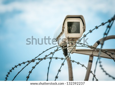 Close up view of security camera hanging among barbwire in prison or other guarded object with blue sky background. Modern ways of supervision. Using new technology in security and safety. #132392237