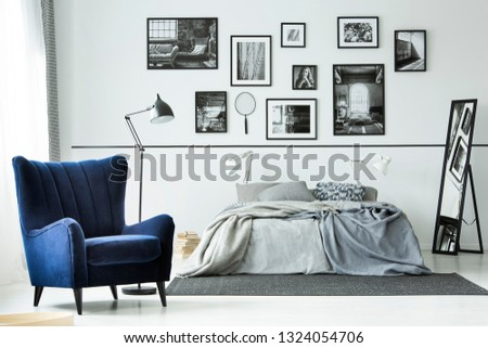 Comfortable blue armchair in monochromatic bedroom interior with king size bed and gallery of posters on the wall #1324054706