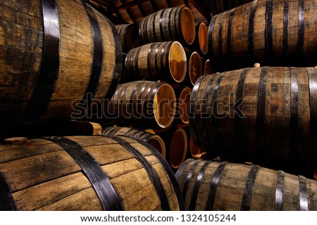 Rows of alcohol barrels in stock. Distillery. Cognac, whiskey, wine, brandy. Alcohol in barrels Royalty-Free Stock Photo #1324105244