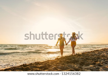 Happy Romantic Middle Aged Couple Enjoying Beautiful Sunset Walk on the Beach. Travel Vacation Retirement Lifestyle Concept #1324156382