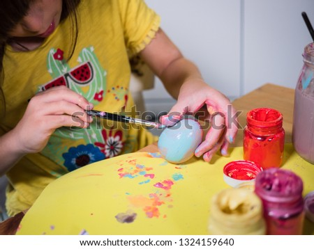 smiling child girl wearing in yellow shirt, she paints Easter eggs at home #1324159640