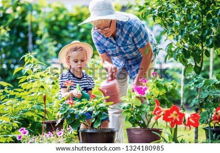 Gardening with kids. Grandmother and her grandchild enjoying in the garden with flowers. Hobbies and leisure, lifestyle, family life #1324180985