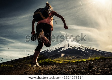 Young woman, trail running athlete runs on the trail with loose ground and volcano on the background #1324278194