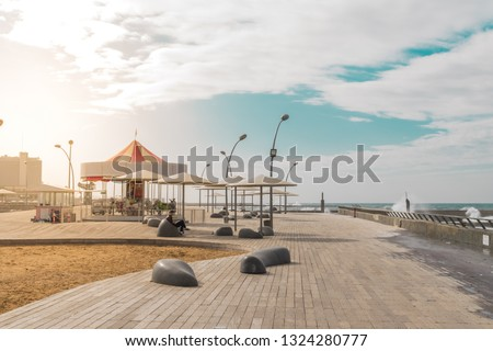 View of Namal promenade at Tel Aviv Port, Israel. Sunset at harbour deck with carousel and sunshades by the sea Royalty-Free Stock Photo #1324280777