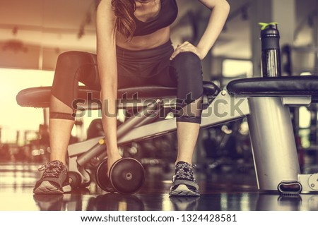 Working out with dumbbell weights at the gym.Fitness Women exercising are lifting dumbbells with a whey protein placed next to the gym.Fitness muscular body.Workout at gym. #1324428581