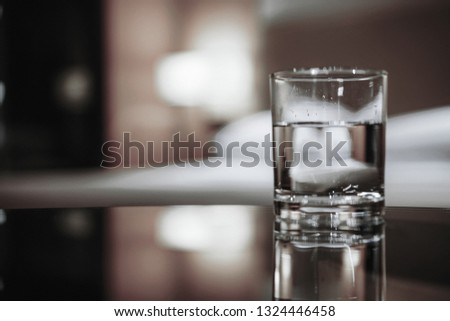 Focus on glass of water. Elegant and comfortable home & hotel bedroom interior with warm lights room as background.  #1324446458