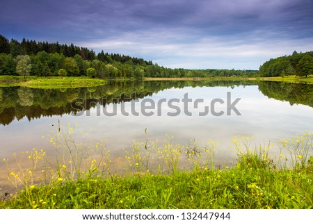 Fantastic landscape with lake and dramatic sky. Overcast sky. Carpathian, Ukraine, Europe. Beauty world. #132447944