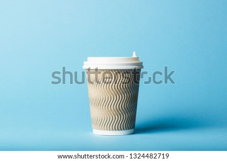 Paper cup with a plastic lid on a blue background. Hot drink concept, tea or coffee, takeaway. #1324482719
