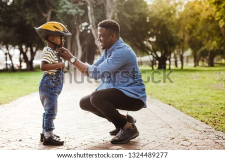 African man putting helmet on cute boy at the park. Father puts his son a protective helmet for riding bike. #1324489277
