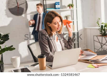 attractive businesswoman holding paper plane and sitting near laptop with coworker on background, procrastination concept #1324581467
