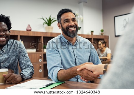 Two business people shaking hands while sitting in meeting room. Middle eastern businessman shake hands to businesswoman. Portrait of happy smiling latin man signing off deal with an handshake. #1324640348
