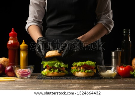 the chef prepares a burger, a hamburger. on a background with ingredients.  #1324664432