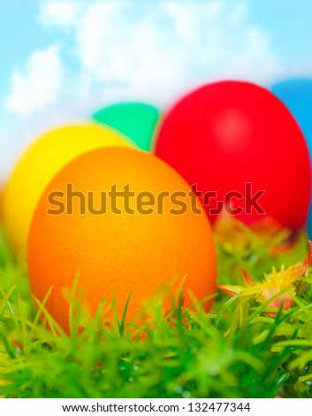 Beautiful painted colorful eggs on fresh green grass over blue sky, happy Easter holiday, religious traditions, spring nature #132477344