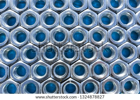 Metal nuts on blue background. Abstract industry background. Natural photo. #1324878827