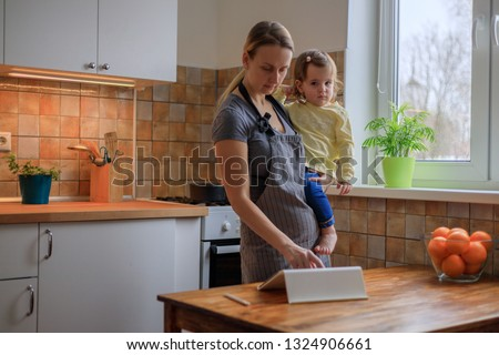 Mother with her baby girl looking for recipe on digital tablet #1324906661