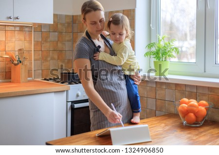 Busy woman working on tablet in kitchen, multi-tasking mom cooking and working #1324906850