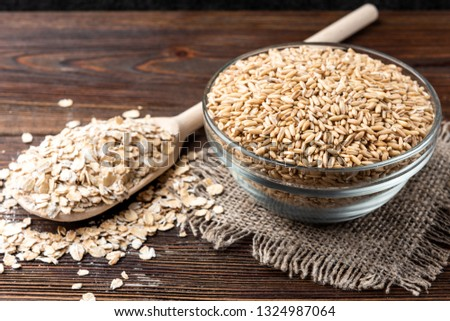 Oats and flakes on dark wooden background. #1324987064