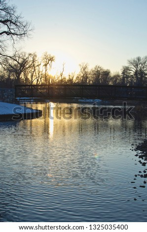 A long view of the cold winter season in the park on the lake in the dusk sunlight.  #1325035400