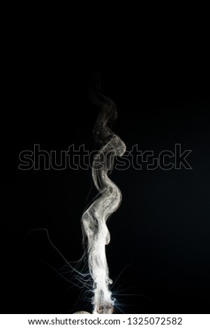 Column of vape clouds splash on black background. A lot of lines of smoke. White fog is tight. Stock isolated white smoke with spray boiling liquid.