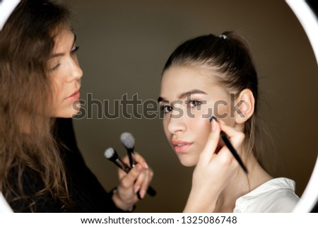 Makeup artist the charming girl is doing makeup to a beautiful young girl #1325086748