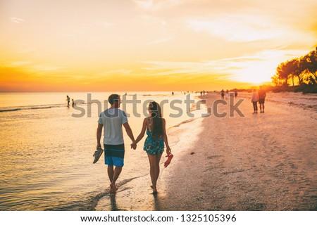 Beach summer beach people lifestyle happy couple enjoying sunset walk on Shelling beach famous tourist destination on the southwest coast of Florida -Gulf of Mexico. Sanibel Island, Florida. #1325105396