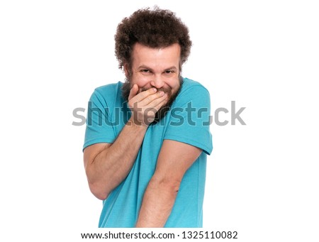 Crazy bearded modest and embarrassed Man with funny Curly Hair, isolated on white background. He is Shy, covering his mouth with hand and looking in camera. Emotions and signs concept. #1325110082