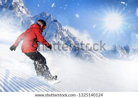 Fast snowboarder riding on slope during beautiful sunny and snowy day in the alpine mountains. #1325140124