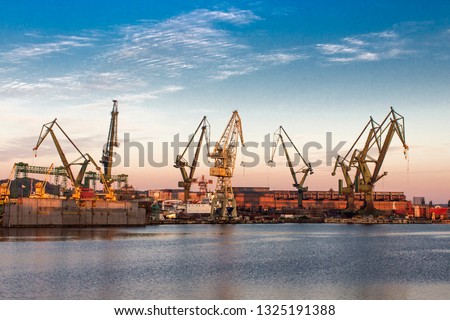 Morning landscape - view of the shipyard with historical cranes in the industrial part of the city Gdansk (Gdańsk) in Poland (Polska). The shipyard is close to the old town. Peaceful Motlawa river. #1325191388