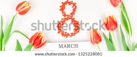 Creative flat lay top view 8 March International Women's Day greeting card with red tulips spring flowers on white background. Celebration banner template #1325228081