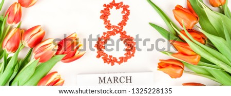 Creative flat lay top view 8 March International Women's Day greeting card with red tulips spring flowers on white background. Celebration banner template #1325228135