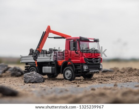 NITRA, SLOVAKIA - FEBRUARY 27 2019: Scale model Mercedes-Benz Actros in communal services. Red truck with stones in dumper. Forklift truck. Red dumper truck. #1325239967