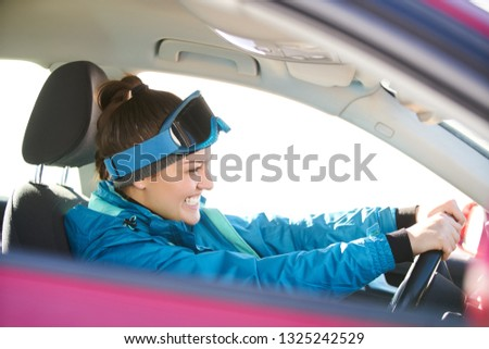 girl driving a car while preparing for skiing on a snowy mountain #1325242529